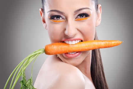 Funny image of woman showing carrot,  Healthy lifestyle people. photo