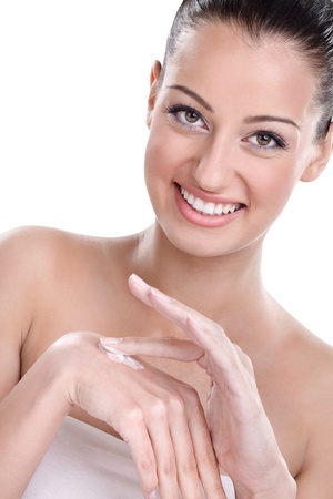 Young beautiful woman applying hands cream photo