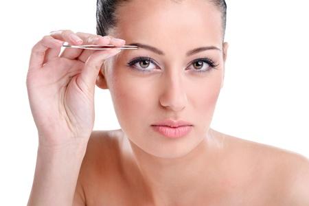 pinzas: Joven y bella mujer depilarse las cejas, mirando a la cámara como espejo