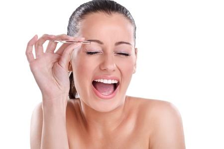 pinzas: Joven mujer hermosa depil�ndose las cejas con las pinzas con un grito de dolor
