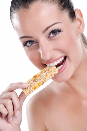 Young pretty woman eating granola bar, isolated on white background photo