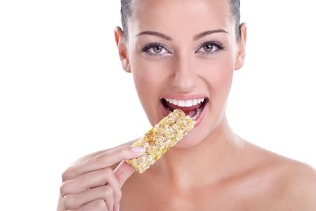 granola bar:  Young healthy woman eating muesli bar snack