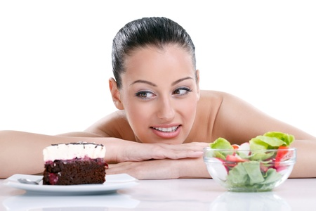 Dieting concept,  beautiful young woman choosing between healthy food and tasty cakes photo