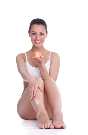 Beautiful pretty young woman caring about her legs with moisturizing cream photo