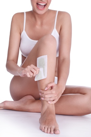 young woman doing depilation for her legs with waxing photo