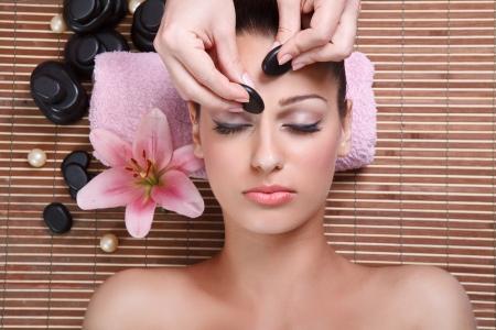 masajes faciales: joven y bella mujer con masaje facial con piedras minerales Foto de archivo