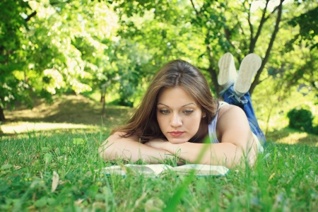 Young beautiful woman relaxing and reading in park   photo