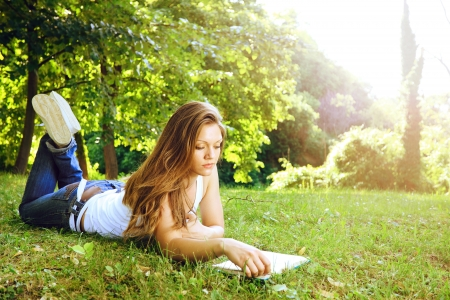 field study: Concentrate beautiful young woman reading in park  Stock Photo