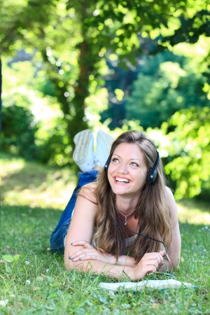 Young woman reading book  and  listening music lying on grass in park photo