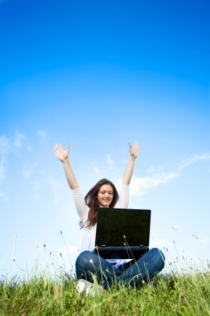 laptop outside: Happy girl with laptop sitting on grass