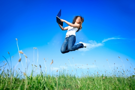 student travel: Woman holding a laptop computer jumping over blue sky