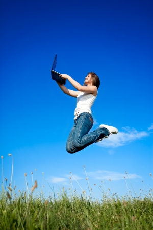 Happiness young girl jumping with laptop over blue sky  photo