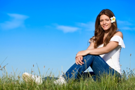 blue sky thinking: Beautiful young  woman sitting on grass and looking at camera