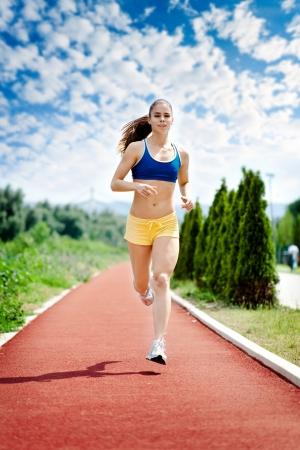 jogging track: runner - woman running outdoors training for marathon run. Beautiful fitness model in her 20s.