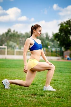 exerting: Young woman runner stretching before running Stock Photo