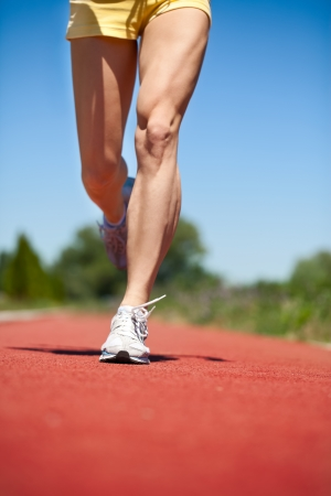 Running legs and shoes of runner in action