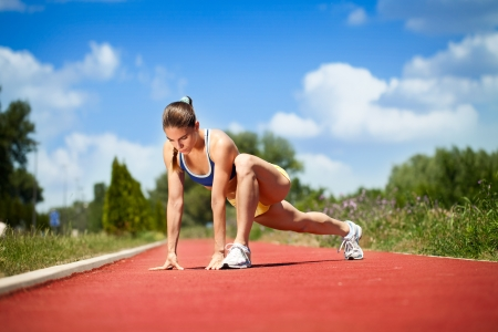 attractive female runner stretching before her workout photo
