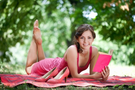 Portrait of a beautiful young woman reading a book while lying on green grass photo
