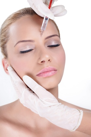 Cosmetic botox injection in the female face, eye and eyebrow zone photo