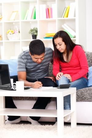 finance problems: young couple calculating their financial budget in living room  Stock Photo