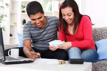 financial planning married:  Smiling young couple deployment of money for bills at home