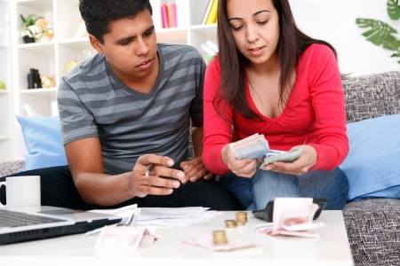 budget crisis: Portrait of a concentrate young couple looking at their home expenses Stock Photo