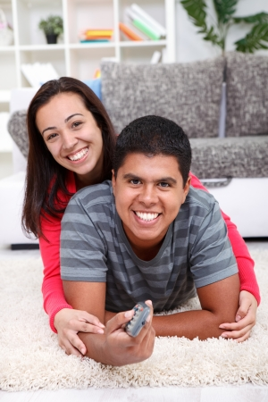 Smiling  couple watching  TV on floor at home photo