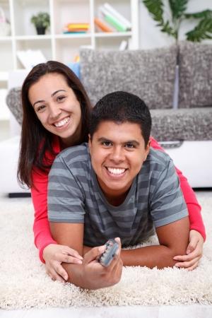 pareja viendo tv: Sonriente pareja viendo la televisi�n en el piso en su casa