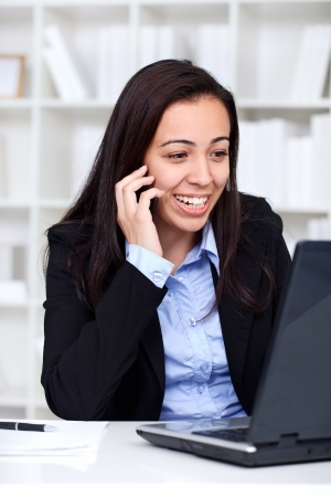 successes:  young businesswoman smiling and talking on phone in office