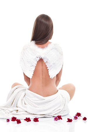 Portrait of young woman wearing angelic wings over white photo