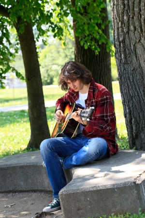 romantic man playing the guitar in park photo