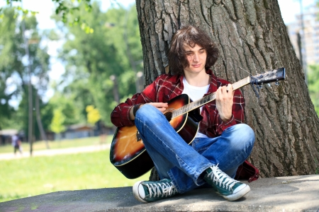 man playing guitar: Young man playing guitar leaning on a tree in the park