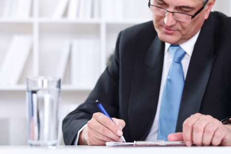 Mature business executive writing on papers at office desk photo