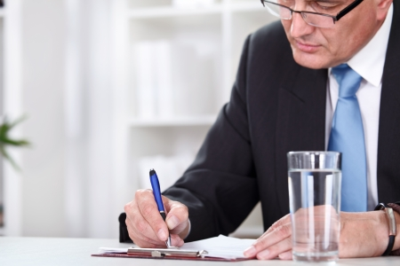 Office desk with business man signing a contract. photo
