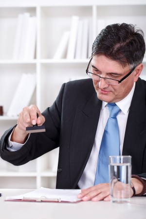 emboutissage: Senior homme d'affaires assis � son bureau et l'estampage de documents