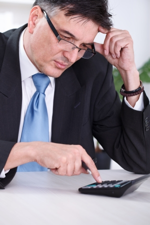 unsatisfied:  Worried senior businessman calculating, unsatisfied with result