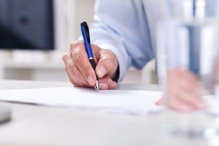 Mannelijke hand schrijven op een papier, het ondertekenen van een contract
