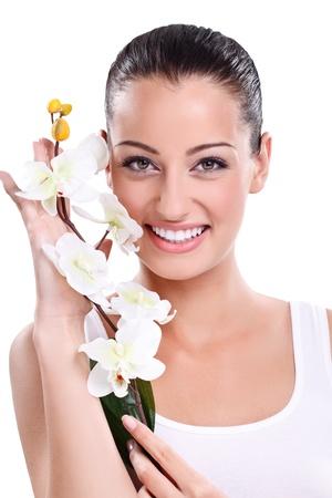 mujeres jovenes desnudas: Hermosa mujer sonriente posando con la orquídea blanca junto a su cara