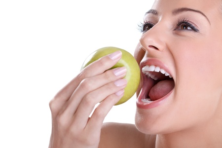 Young woman with healthy tooth biting green apple