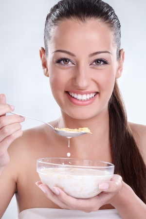 Beautiful healthy woman eating cornflakes and showing her bowl with milk and cereals  photo