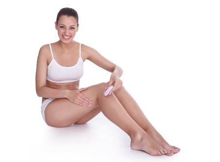 smiling woman depilating her legs with electric razor photo