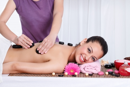 Close up of a smiling woman relaxing on a lounger during a massage in a wellness center Stock Photo - 14734774
