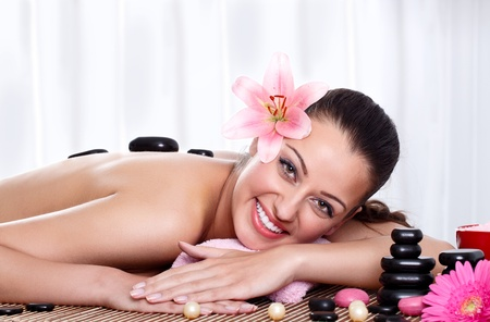Smiling female face - Hot stone massage in the day spa - Portrait of a beautiful young girl at the day spa with black stones on her bare back Stock Photo - 14734746