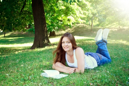 young woman lying on grass in park and reading book  photo