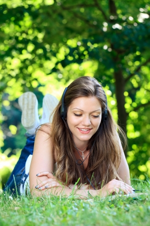 young woman listening music on the grass using headphones and reading book photo