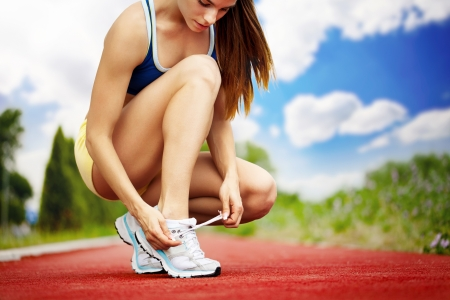 shoelaces: Athlete girl trying running shoes getting ready for jogging Stock Photo