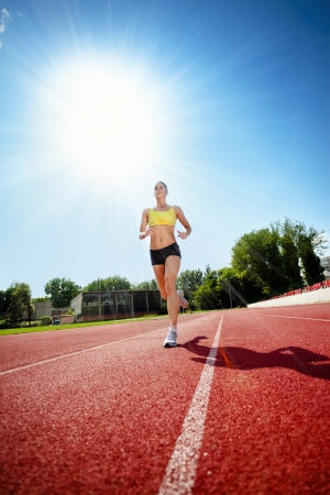 young woman exercising jogging and running on athletic track photo