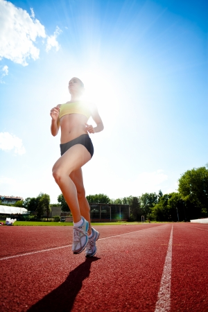 jogging track: Young sporty woman running on sunny day