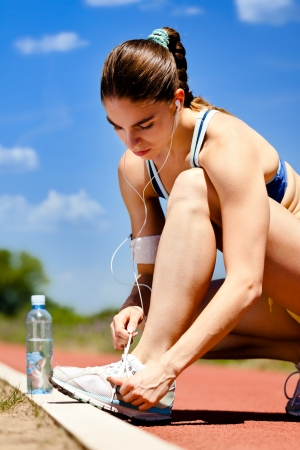 shoelaces:  Woman tying her shoelaces before starting her workout