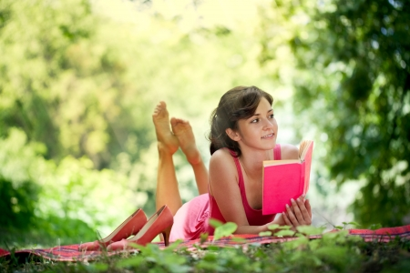 Beautiful woman with a happy face and reading in nature